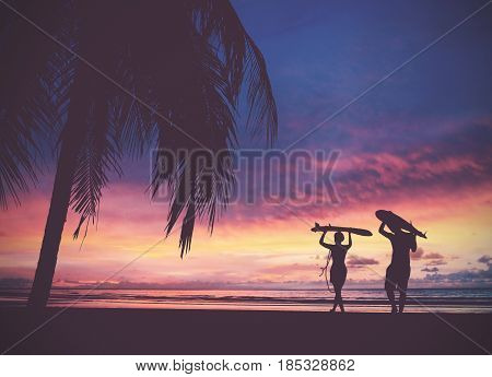 Silhouette of surfer people carrying their surfboards on sunset beach vintage filter effect