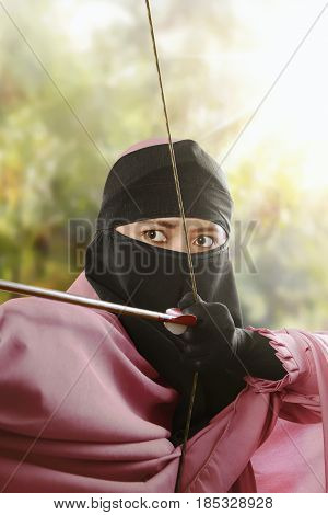 Close up asian muslim woman with bow ready to shoot an arrow in the park