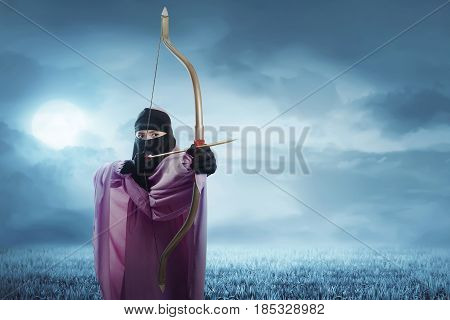 Young Asian Muslim Woman In Hijab Ready To Shoot An Arrow