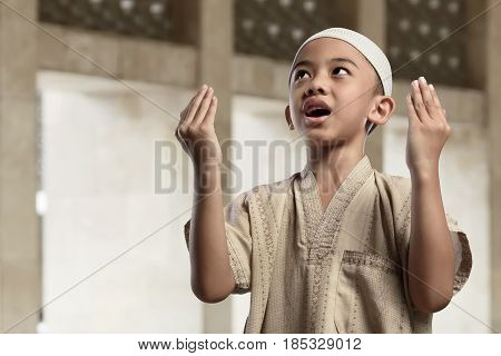 Little Asian Muslim Boy Is Praying With Raise Hand