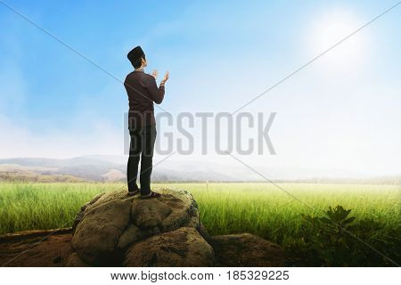 Handsome Asian Muslim Man Praying With Standing On Stone