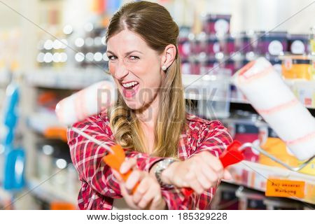 Young woman in decoration department of hardware store with paint rollers