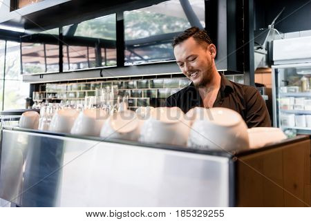 Happy Asian young man looking down while working as barista behind the bar counter of a modern cafeteria