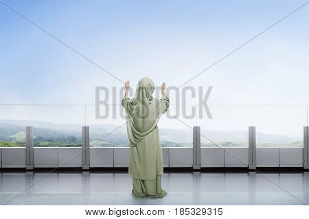 Rear View Of Asian Muslim Child Raising Hand And Praying