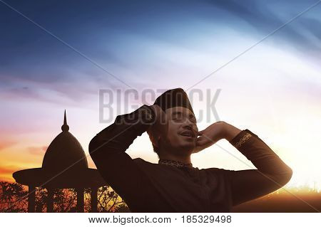 Religious Asian Muslim Man In Traditional Dress Praying To God