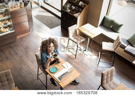 Top view of cheerful girl drinking mug of beverage while locating at table in confectionary shop. She looking at camera
