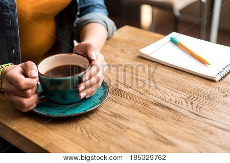 Focus on close up female arms keeping cup of delicious coffee. Woman tasting it in cafe