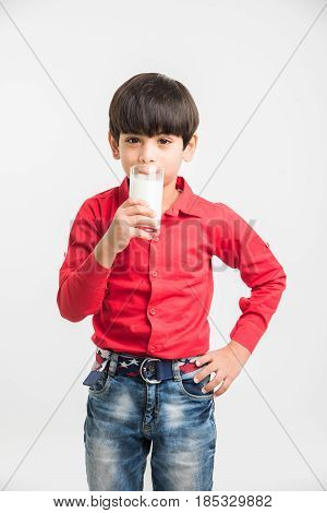 cute little indian boy drinking plain milk or holding a glass full of milk, over white background