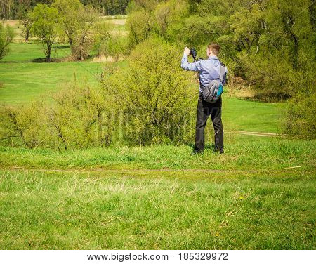 A young guy with a camera in his shirt and trousers takes pictures in the open air