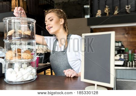 Smiling waitress taking pastry for visitor in modern candy store
