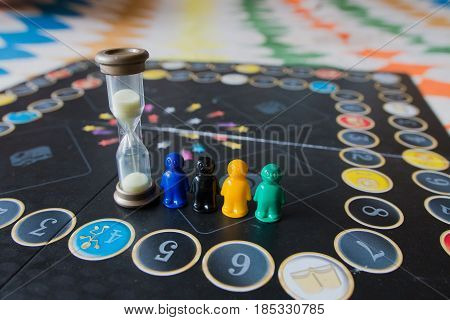 Multi-colored Chips For Tabletop Game In The Form Of Little Men And An Hourglass