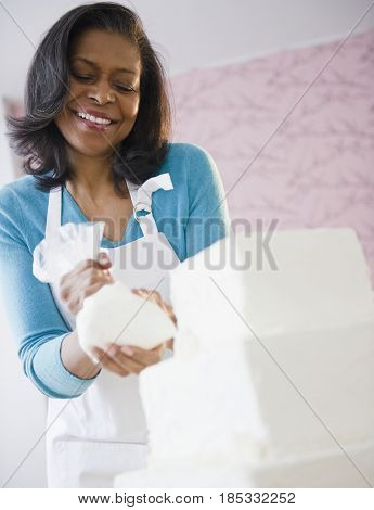 Mixed race woman icing a cake