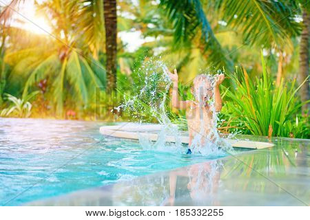 Happy boy having fun in swimming pool, joyful kid splashing water from the pool, spending summer holidays on the luxury beach resort