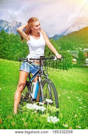 Happy fit woman on a bicycle traveling along mountainous village, healthy lifestyle, recreation in Alps, Austria, Europe