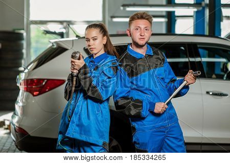 Man and woman auto mechanics in a car workshop at work
