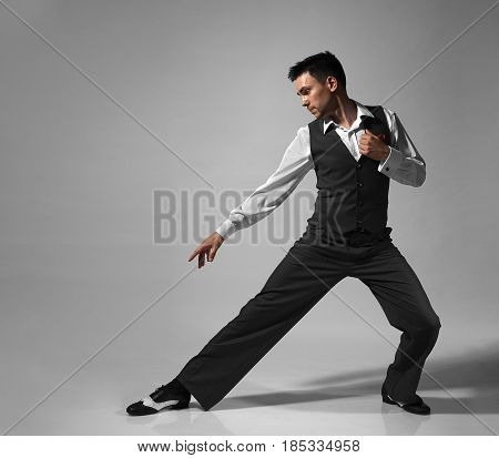 Young male professional dancer dancing in studio on gray background.
