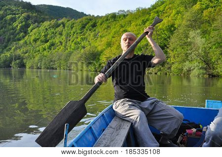 Man rowing in small fishing boat with a wooden paddle.  Man in a small boat on the lake