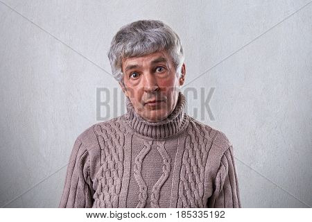 A Surprised Old Man With Dark Eyes Having Wrinkles On His Face And Gray Hair Wearing Brown Sweater L