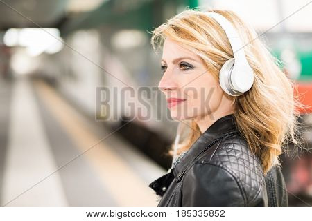 Woman Listening Music at the Train Station