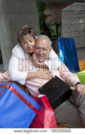Senior Hispanic woman hugging husband surrounded by gifts