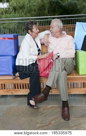 Senior Hispanic couple sitting on bench with gifts