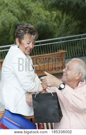 Senior Hispanic man handing shopping bag to wife