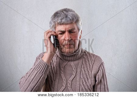 An Angry Mature Man With Gray Hair And Wrinkles Holding Smartphone In His Hand Communicating With Hi