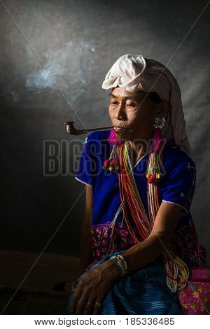 CHIANG MAI THAILAND - JUL 25 : Karen hill tribe is smoking tobacco pipe with traditional clothes and dramatic light on July 25 2015 in Chiang Mai Thailand.