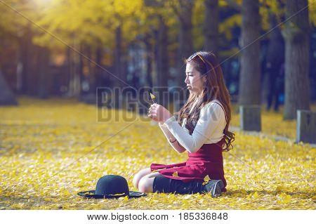 Beautiful Girl With Yellow Leaves In Nami Island, Korea. Nami Island In Autumn. Vintage Tone Style.