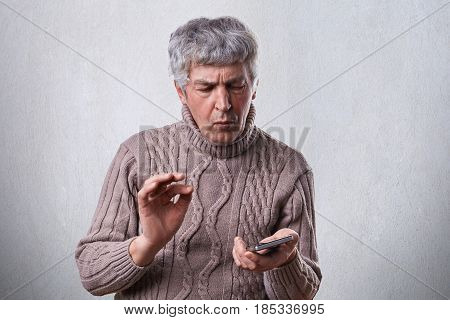 A Puzzled Mature Man In Brown Sweater Holding Smartphone Trying To Understand How To Switch It On. T