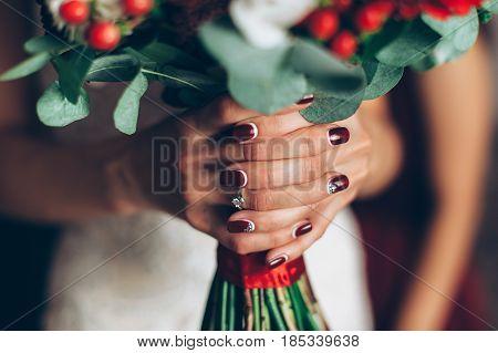 wedding red bouquet in hands of the bride