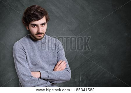 A Portrait Of Serious Young Bearded Guy With Stylish Hairstyle Dressed In Casual Sweater Standing Cr