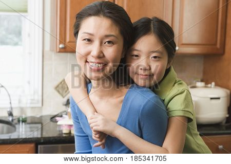 Asian girl hugging mother in kitchen