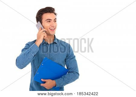 side view of a young student speaking on the phone and looks away from the camera on white background