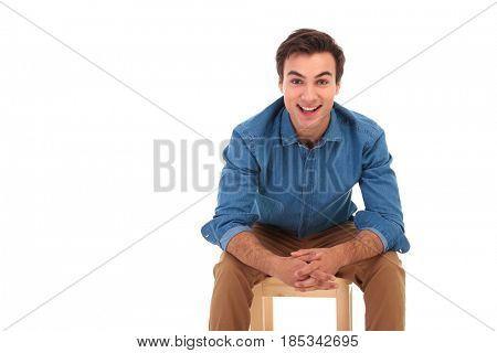 smiling casual man resting elbows on knees while sitting on chair on white background