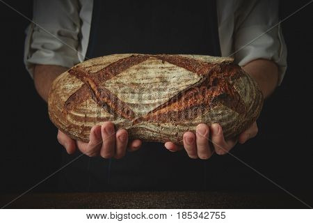 Baker's hands hold an oval bread.
