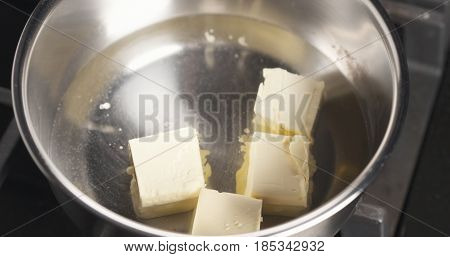 Handheld shot of shot of adding butter into water, 4k photo