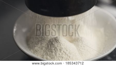 Handheld shot of sieving flour with mug sieve on plate closeup, 4k photo