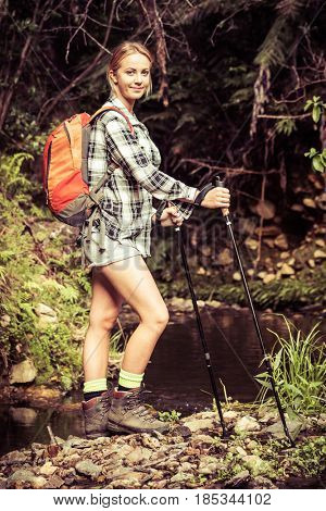 Young woman hiking by stream