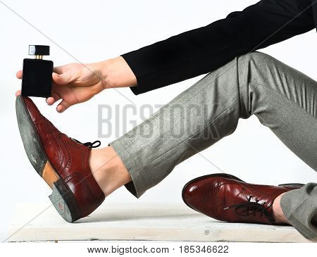 Strong Male Legs And Hand Holding Perfume On Wooden Bench