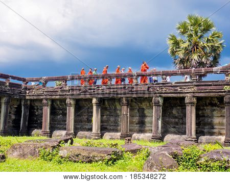 Siem Reap Cambodia - October 30 2016: Buddhist monks and novices walking on the stone bridge to enter Angkor Wat UNESCO World Heritage site in Cambodia