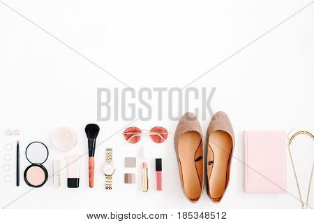 Beauty blog fashion concept. Female pink styled accessories: watches sunglasses cosmetics shoes on white background. Flat lay top view trendy feminine background.