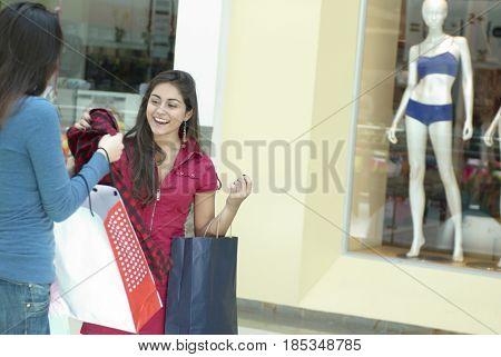 Hispanic friends shopping in shopping mall