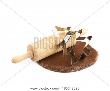 Rolled up thin layer of cookie dough with a wooden rolling pin and a cookie cutter over it, composition isolated over the white background