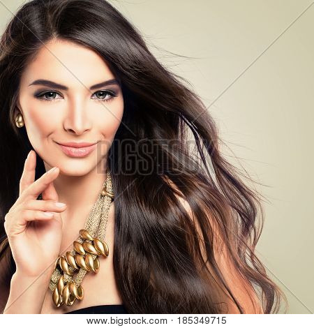 Glamorous Brunette Woman Fashion Model with Blowing Wavy Hairstyle Makeup and Golden Necklace. Beautiful Girl with Long Healthy Hair Smiling