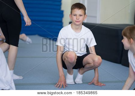 The Young Man Performs Gymnastic Exercises In The Gymnasium.