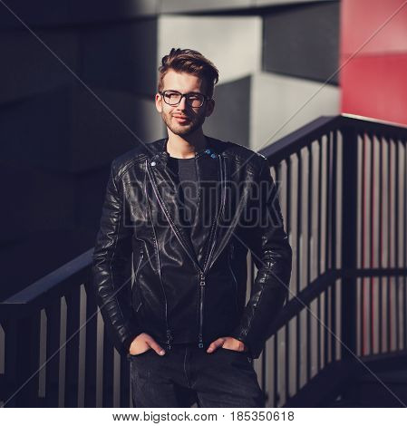 Funny smiling hipster handsome man guy in jacket and glasses posing in city