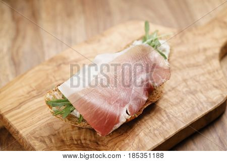 italian sandwich with speck and arugula salad, shallow focus