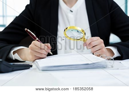 internal audit concept - woman with magnifying glass inspecting documents