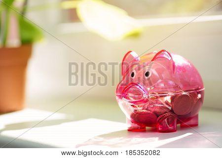 house savings - piggy bank on window sill